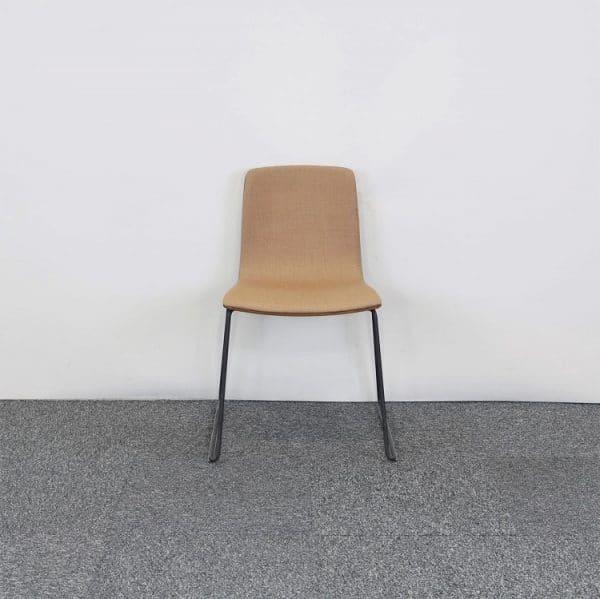 Träfärgad stol från Arper syns framifrån