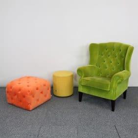 Möbelgrupp med två sittpallar och en fåtölj i starka färger