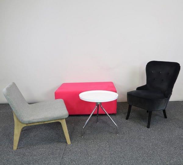 Loungegrupp med bord, rosa puff och svart fåtölj.