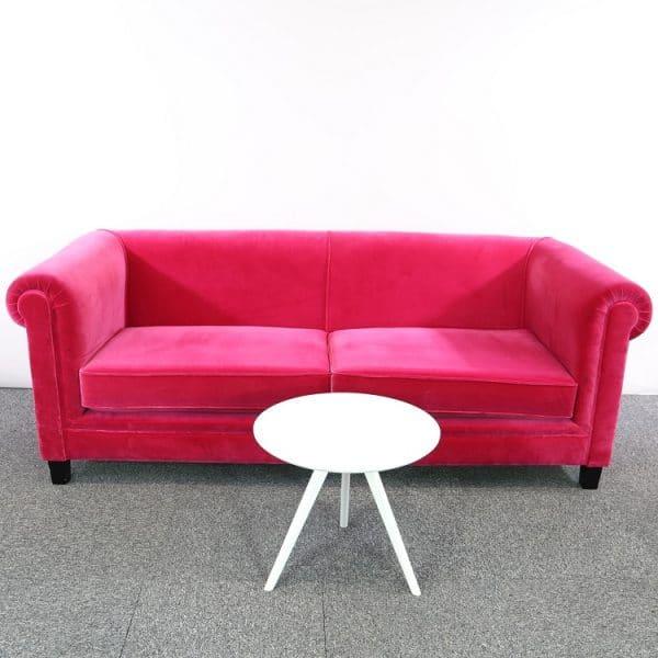 Rosa soffa i sammet från deNONA står bakom ett litet runt bord