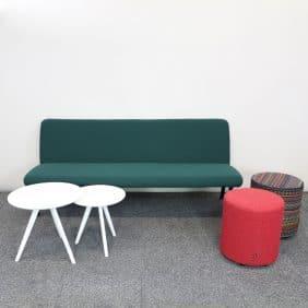 Loungegrupp med grön soffa, två sittpuffar och två vita små runda bord